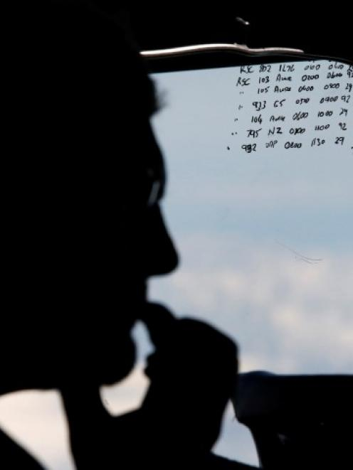 A crew member aboard a Royal New Zealand Air Force P-3K2 Orion aircraft takes part in the search...