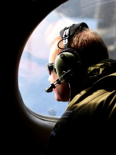 A crew member looks out an observation window aboard a Royal New Zealand Air Force P3 Orion...