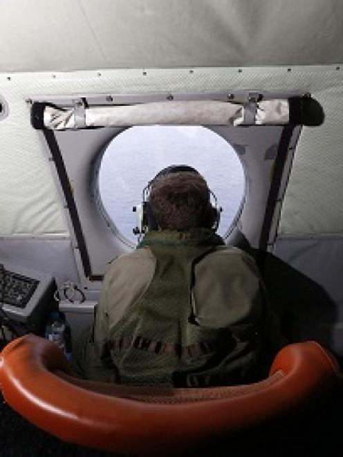 A crewman aboard a Royal New Zealand Air Force P-3K2 Orion aircraft scans the ocean for missing...