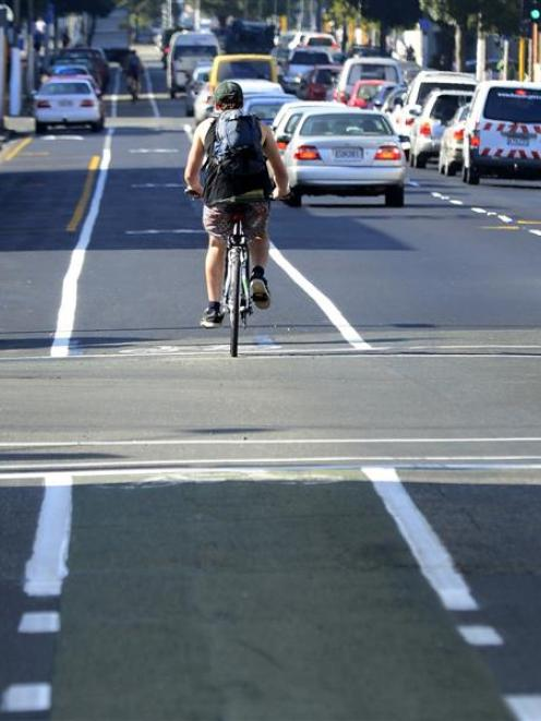 A cyclist heading north on Cumberland St, a Dunedin one-way street, passes St Andrew St and...