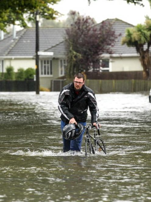 A cyclist wades through flooded streets in Edgeware, Christchurch yesterday. Photo by Getty