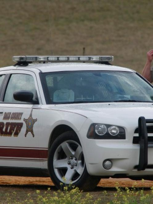 A Dale County Sheriff's deputy stands at a roadblock near the scene of a shooting and the...
