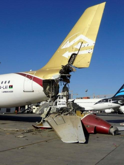 A damaged aircraft sits on the ground after shelling at Tripoli International Airport. REUTERS...