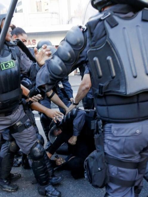 A demonstrator (C, rear) is detained by riot police before the 2014 World Cup final between...