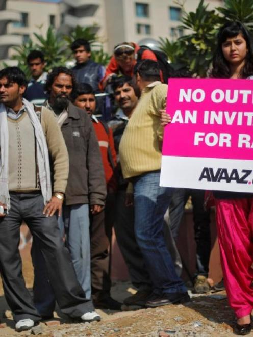 A demonstrator holds a placard during a protest outside a court in New Delhi yesterday. REUTERS...