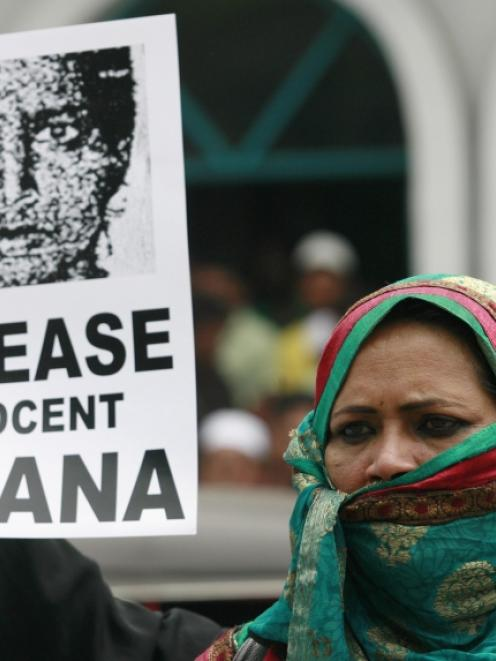 A demonstrator holds an image of Rizana Nafeek, jailed in Saudi Arabia on charges of murdering a...