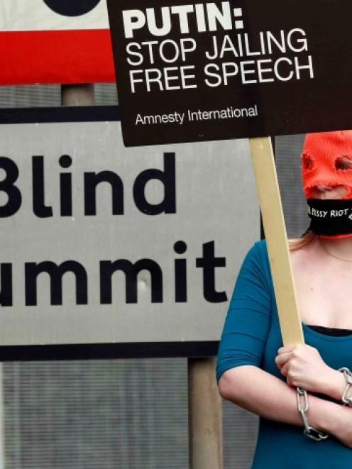 A demonstrator wears a 'Free Pussy Riot' balaclava as she protests at the security fence...