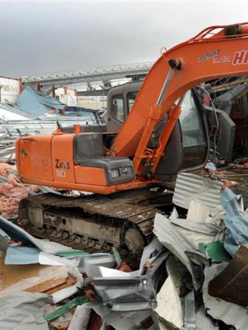 A digger sits among the rubble of what was Stadium Southland after demolition work was halted...