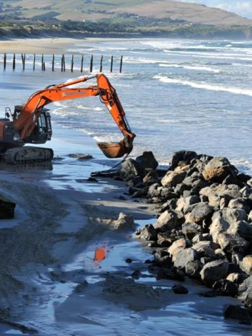A ditch-digger works on a pile of rocks on St Clair Beach yesterday. Photos by Craig Baxter.