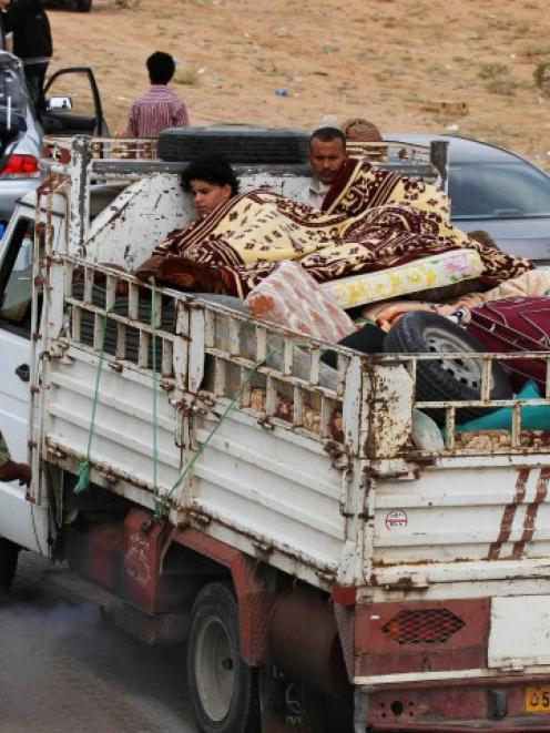 A family fleeing the fighting in Sirte is pictured at a checkpoint 4km outside the city...