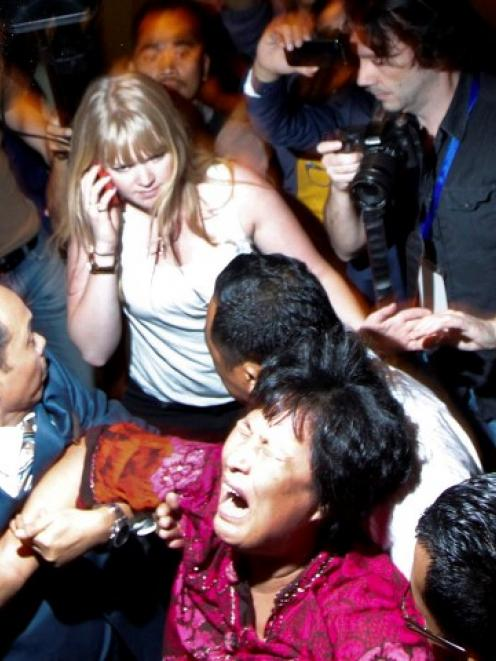 A family member of a passenger onboard the missing Malaysia Airlines Flight MH370 screams as she...