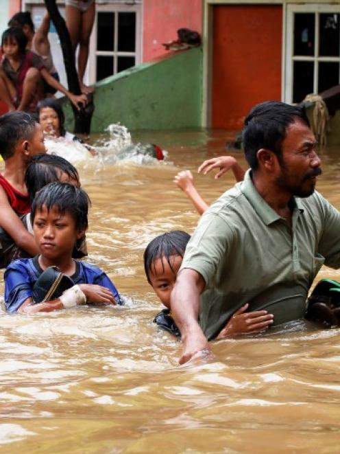 A father escorts his son as they evacuate a flooded area in Jakarta. REUTERS/Enny Nuraheni