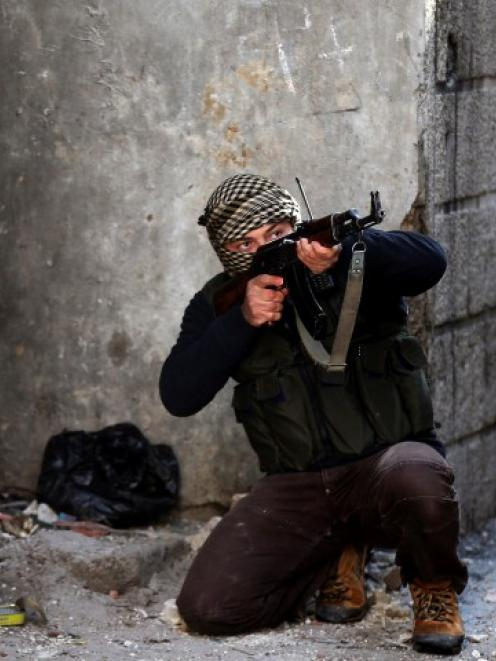 A fighter from the Sadik unit of Free Syrian Army's Tahrir al Sham brigade aims his rifle in...
