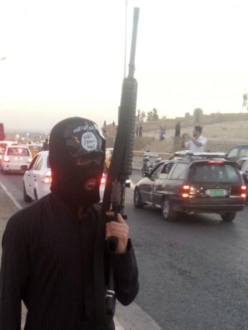 A fighter of the Islamic State of Iraq and the Levant (ISIL) stands guard with his weapon by the...