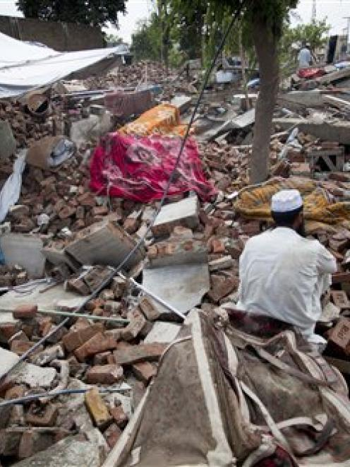 A flood-affected man sits over debris of his house collapsed by flooding in Nowshera, northwest...