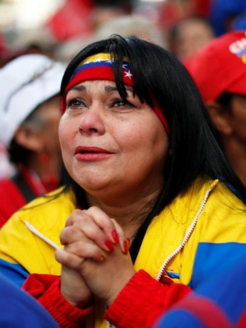 A follower of Venezuelan President Hugo Chavez prays for his health at Plaza Bolivar in Caracas....