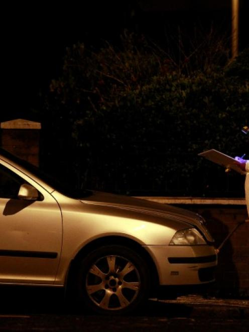 A forensic officer works around a burnt-out unmarked police car in East Belfast after protesters...