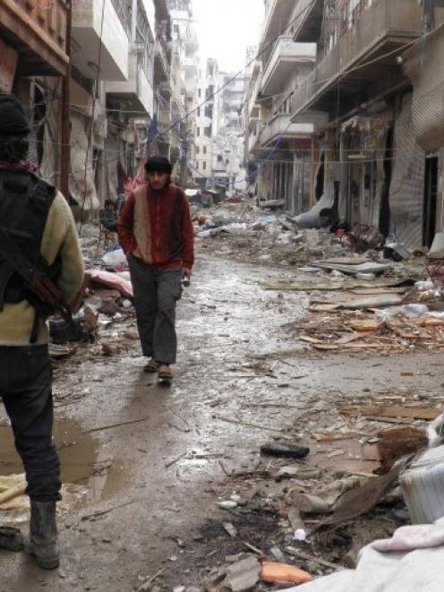 A Free Syrian Army fighter carries his weapons along a street in the besieged area of Homs....