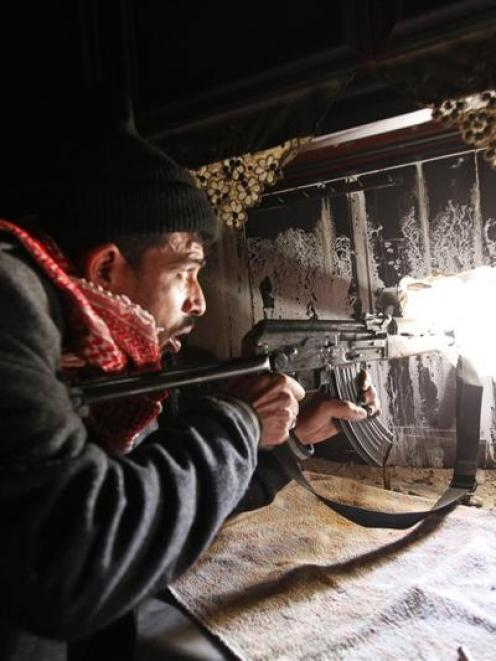 A Free Syrian Army fighter takes up position inside a burnt room in the Aleppo district of...