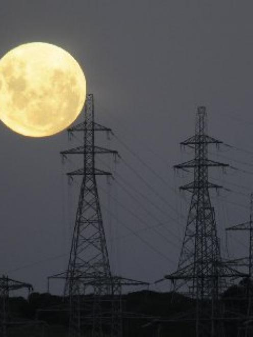 A full moon rises over transmission pylons at Three Mile Hill, near Dunedin. Photo by Stephen...