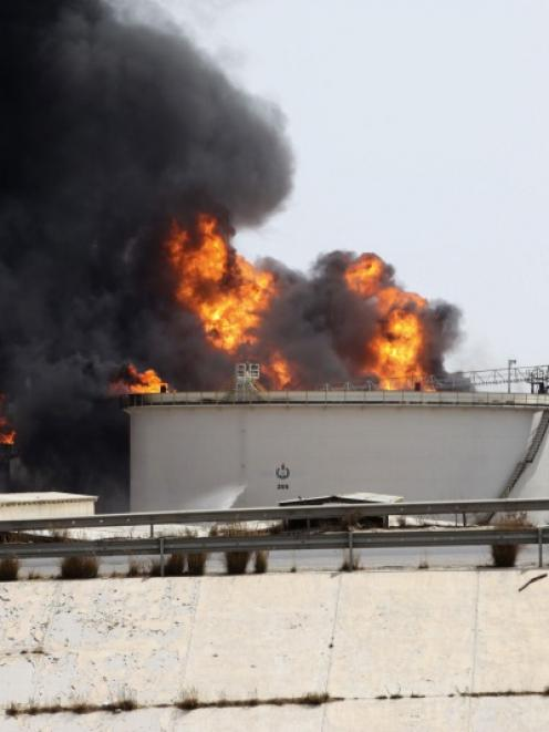 A general view shows fire burning at a fuel depot near the airport road in Tripoli. Photo by Reuters