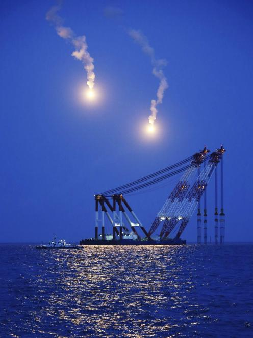 A giant offshore crane which will be used in a night rescue operation, is seen near flares at the...