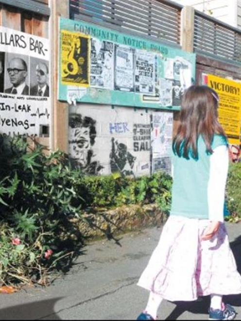 A girl walks past a fence full of posters and notices. Image created by graphic artist Alistair...