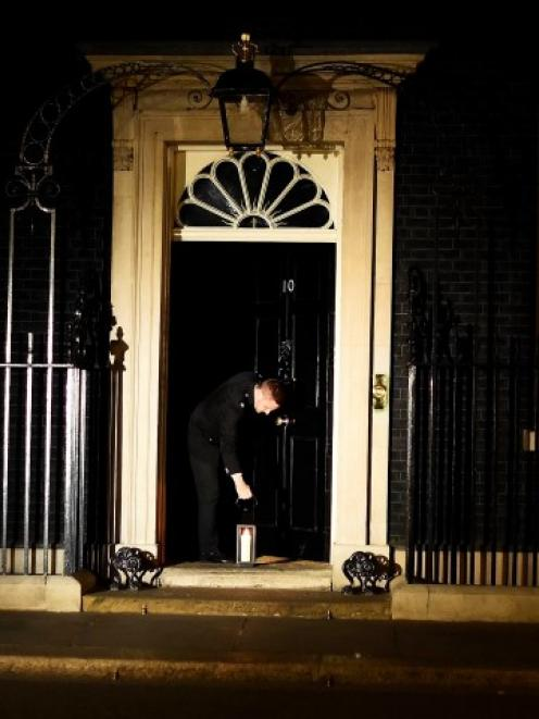 A guard places a lantern at the front door of Number 10 Downing St during 'Lights Out', as part...