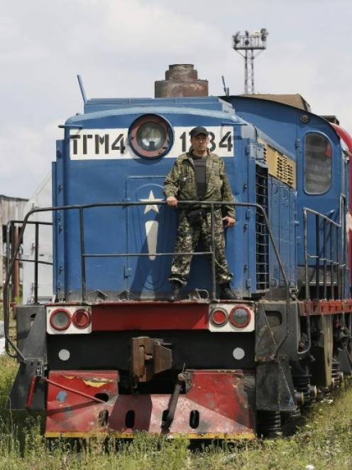 A guard stands on a train carrying the remains of victims of Malaysia Airlines MH17 downed over...