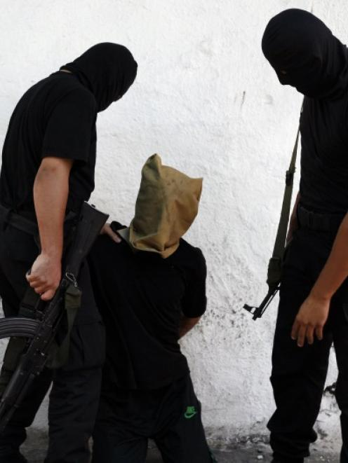 A Hamas militant grabs a Palestinian suspected of collaborating with Israel, before being...