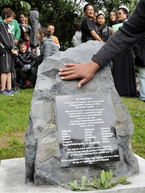 A hand touches a memorial stone during a ceremony at the Southern Cemetery in Dunedin yesterday....