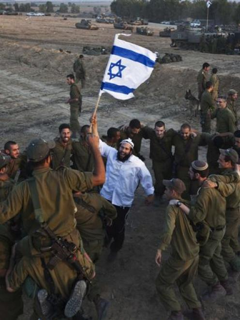 A Hasidic Jew  waves an Israeli flag as he dances with Israeli troops yesterday during a visit to...