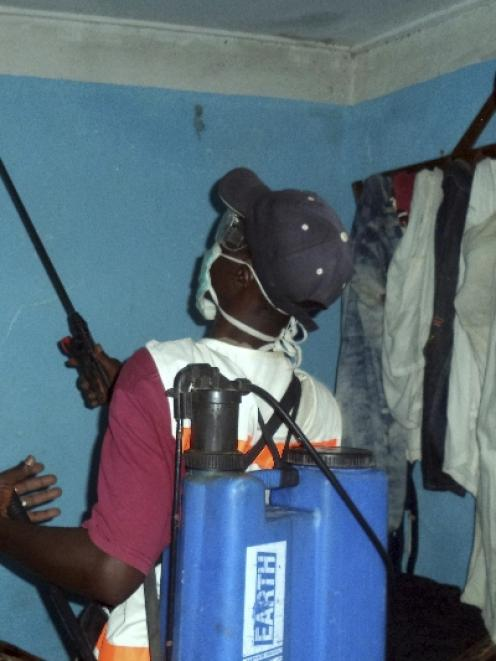 A health worker sprays disinfectant in a house belonging to someone suspected of coming into...