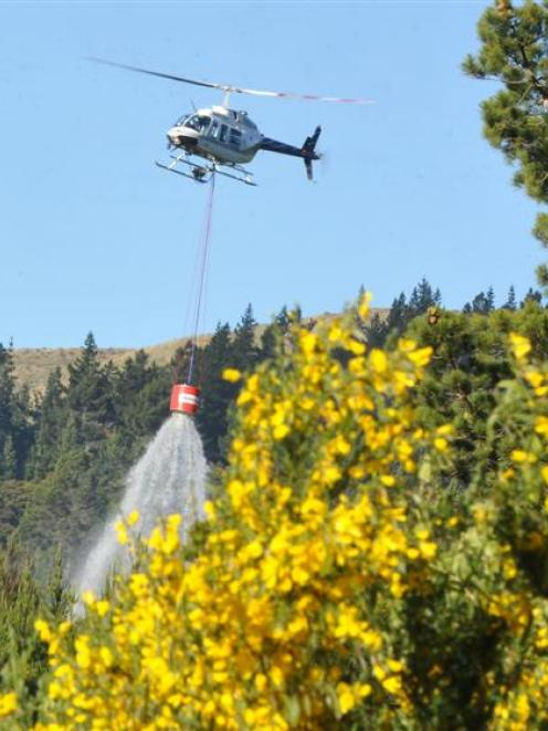 A helicopter-borne  monsoon bucket is used to dampen the remains of a forest fire near Dunedin on...