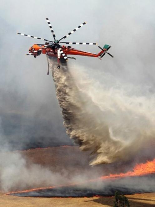 A helicopter dumps water on a bushfire burning in the Grampians bushland in Victoria. REUTERS...