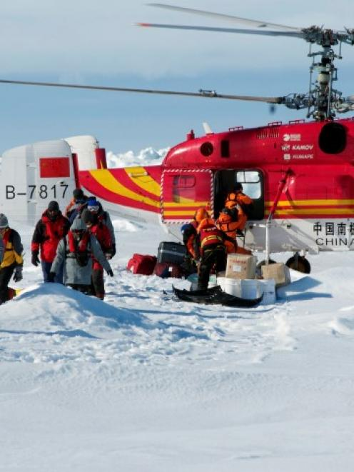 A helicopter from the Xue Long (Snow Dragon) Chinese icebreaker unloads rescued passengers from...