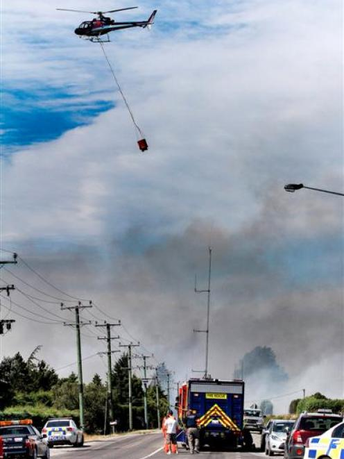 A helicopter with a monsoon bucket flies to a scrub fire in Shands Rd in the Prebbleton area of...