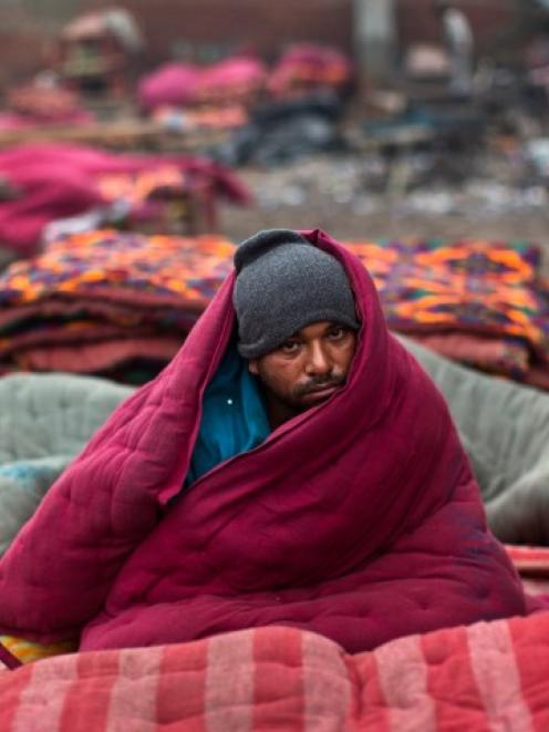 A homeless man wrapped in a quilt sits in an open space on a cold winter morning in the old...