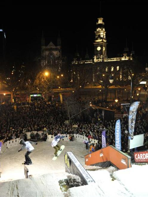 A huge crowd of spectators watches the freestyle antics of skiers and snowboarders at the Octagon...
