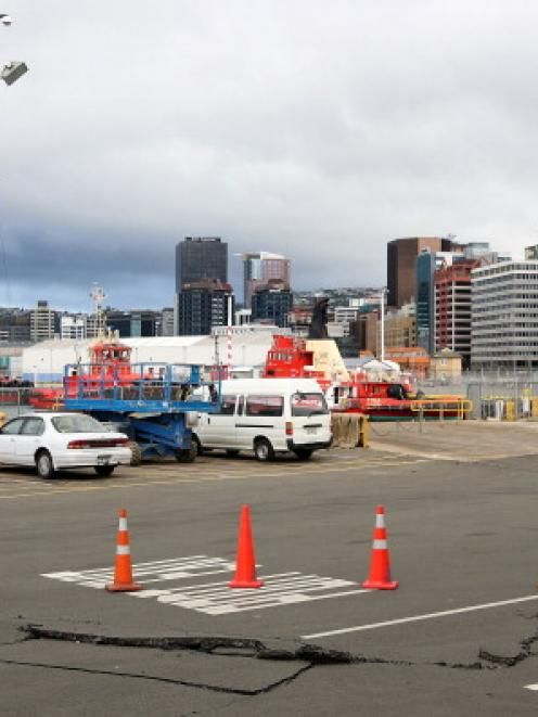A large crack in the road is blocked off by cones at King Edward Wharf in Wellington.  (Photo by...