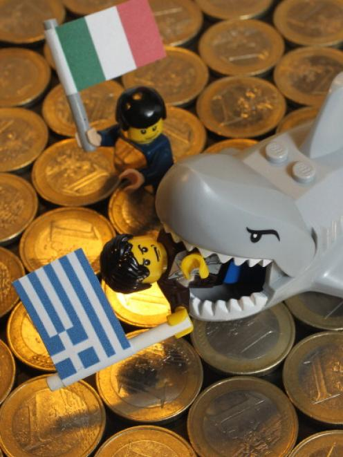 A Lego shark chomps down on a Lego figure holding a Greek flag as another figure holding an...