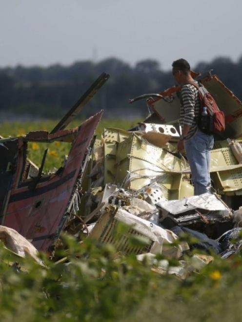 A Malaysian air crash investigator (right) inspects the crash site of Malaysia Airlines Flight...
