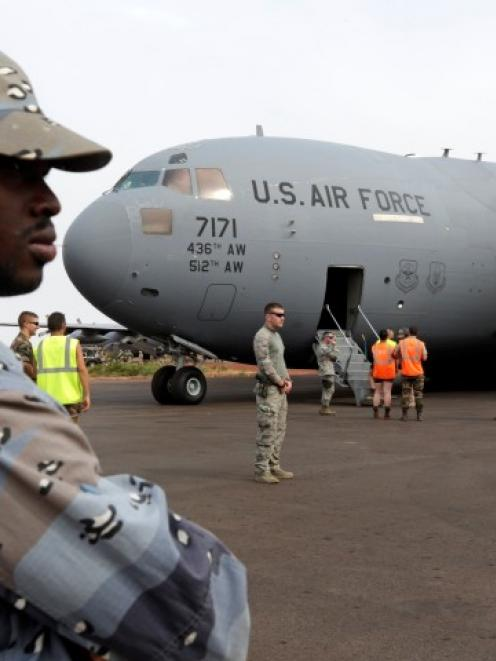 A Malian gendarme stands guard after the arrival of a US Air Force C-17 transport plane with...