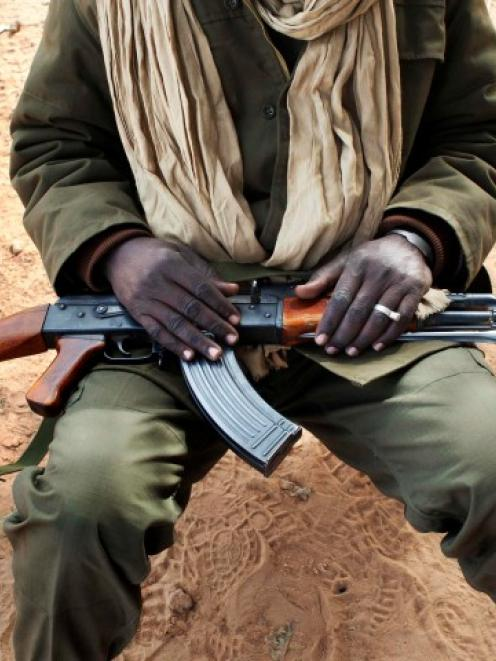 A Malian soldier holds an AK-47 in his lap at a military checkpoint in Diabaly. REUTERS/Joe Penney
