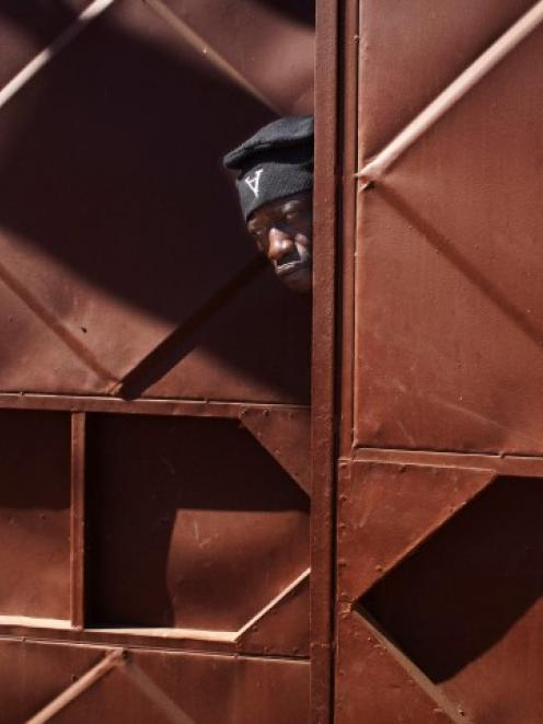 A Malian soldier peeks through a doorway behind which Malian and French soldiers are stationed in...