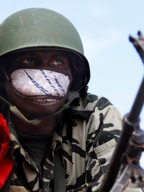 A Malian soldier stands guard with his machine gun on the road between Konna and Sevare. REUTERS...