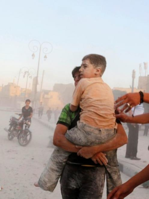 A man carries an injured child at a damaged site hit by what activists said were two barrel bombs...