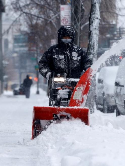 A man clears snow with a snow blower in the South Bronx section of New York City. REUTERS/Mike Segar