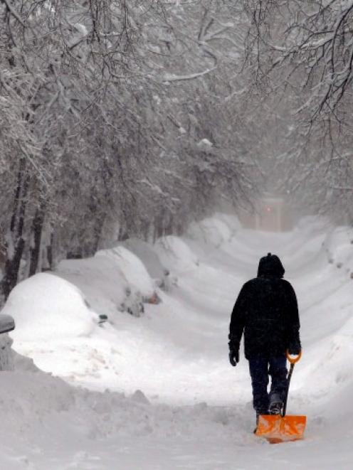 A man drags a shovel up Beacon Hill during a severe snowstorm in Boston, Massachusetts. REUTERS...