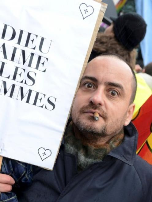 A man holds a sign which reads 'God likes Men' as people in Nice march in support of the French...